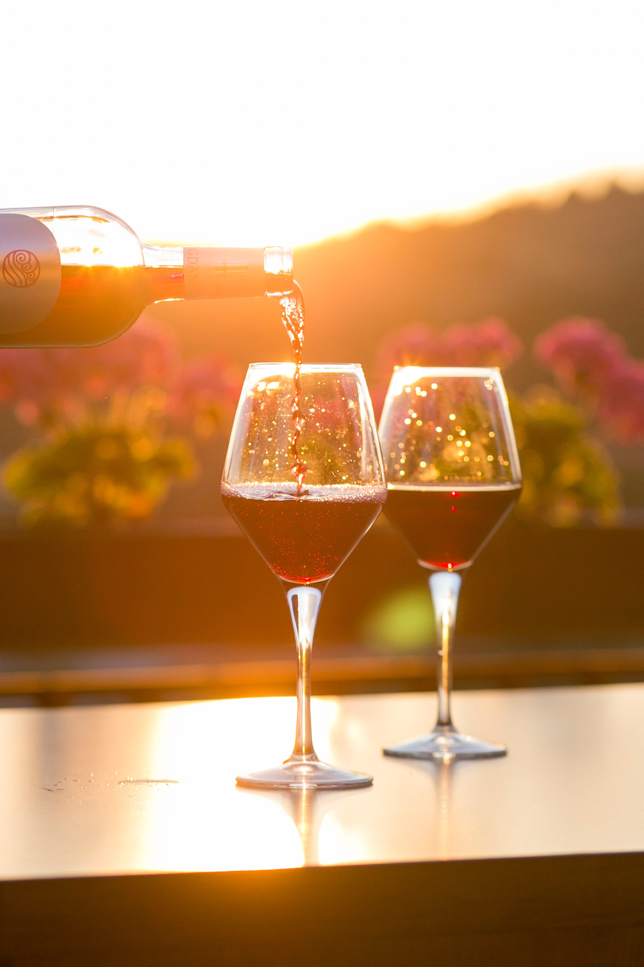 Wine being pour into two glasses on a deck during sunset